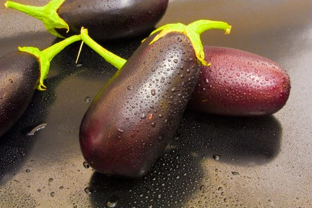 Two eggplant in the center of juicy kali water on a black background