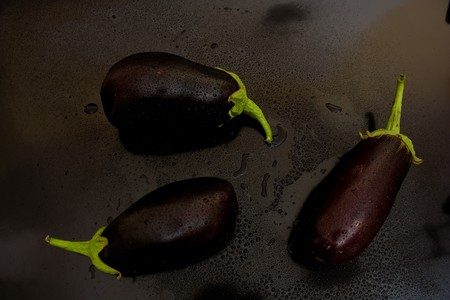 Three of eggplant in a chaotic manner above, with juicy drops of water on a black background photo