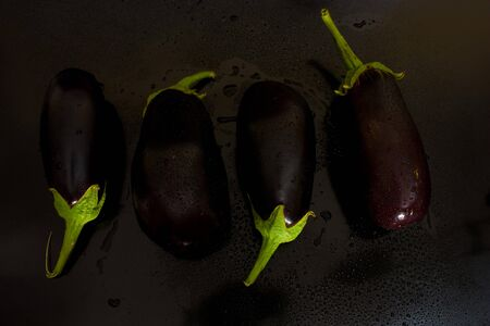 Four of eggplant in a chaotic manner above, with juicy drops of water on a black background photo