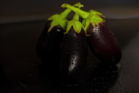 three eggplant stacked vertically on blfck background with drops of fresh water photo
