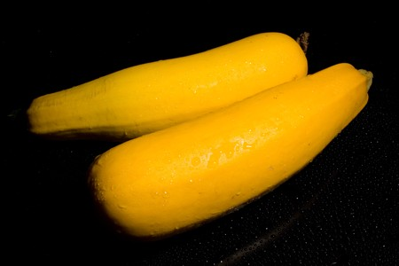 two squash vegetables on a black background with water drops of fresh juicy yellow photo
