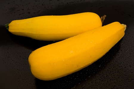 two squash vegetables on a black background with water drops of fresh juicy yellow Stock Photo