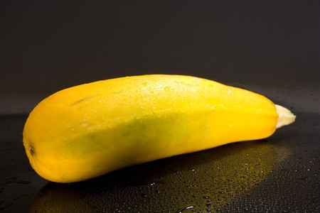 vegetable marrow on a black background with water drops of fresh juicy yellow