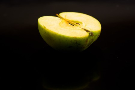 wet juicy green apple half on a black background with drops of juice is highlighted in bright photo