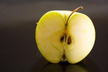 noyau: pomme verte juteuse humide, la moiti� sur fond noir avec gouttes de jus est mis en surbrillance dans le vif