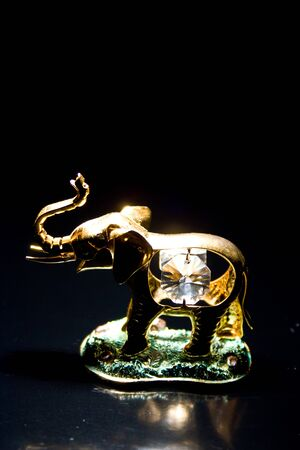 Jewellery gold statuette elephant crystals on a black background photo