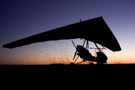 evening silhouette of a hang-glider on the ground after use