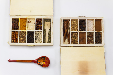 Assortment of spices in wooden box on whie background