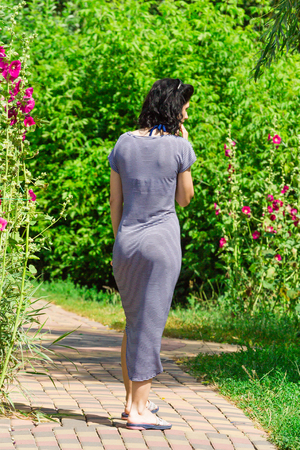 A sexy girl in a tight sea dress, walking along a stone path, a back view. summer Stock Photo