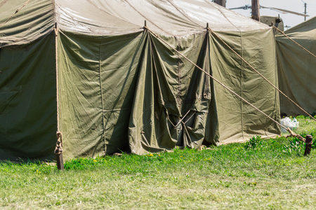 Detail with the exterior of a green military tent. summer