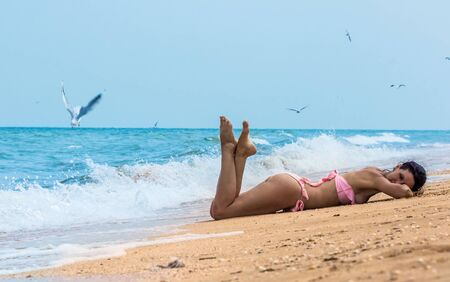 pink bikini: young brunette woman wearing a pink bikini lying on the beach, the ocean, while the gulls fly around her
