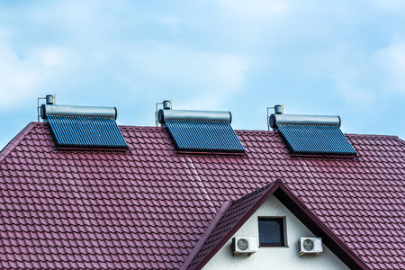 voltaic: Vacuum collectors- solar water heating system on red roof of the house.