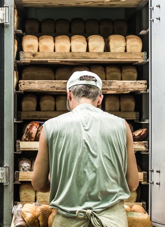 unsliced: shelves full of various bread. Man takes them from the machine