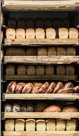 unsliced: Various bread type on shelf. Bakery car