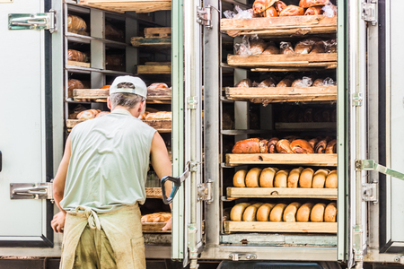 shelves full of various bread. Man takes them from the machine