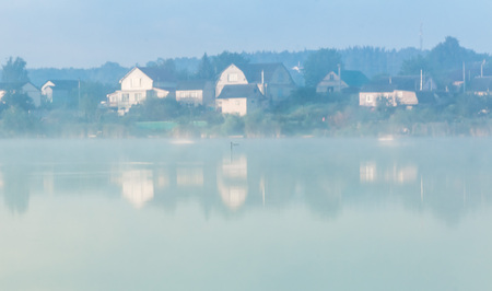 mystic fog is running on the lake in the cold summer morning.