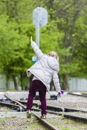 One teen girl balancing away on rail with trees behind