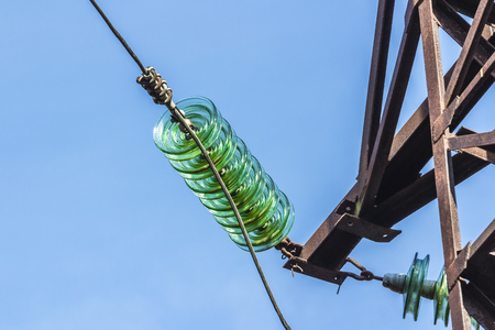Pillar of electricity transmission line with transparent insulators. Photographed close-up against the blue sky Stock Photo