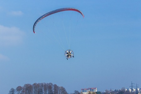 Adventure man active extreme sports pilot flying in the sky with paramotor paraglider paraglider motor. Stock Photo