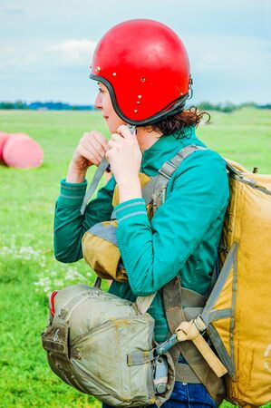 A civilian, young girl, with a parachute dressed, stands on the grass, fastens a red helmet, before jumping