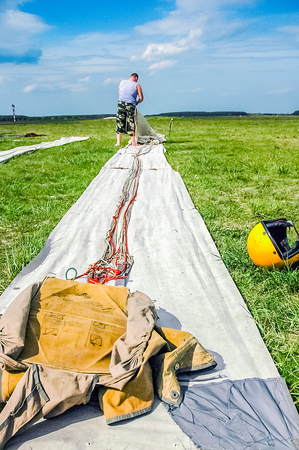 A man, a paratrooper, collects on the grass, a parachute, for a further jump
