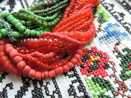 Green and red beads necklace on authentic ukrainian embroidery shirt.