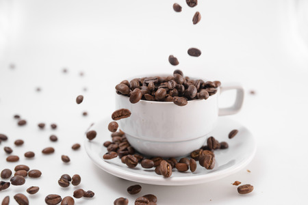 coffee grounds: pour coffee grounds into the cup is isolated on a white background Stock Photo