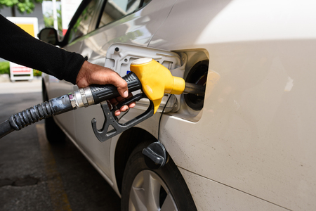 service station: Hand refilling the car with fuel, focus hand