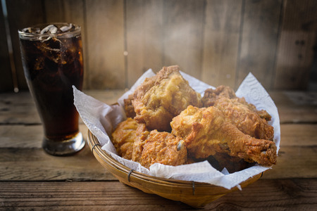 chickens: Fried Chicken with slightly smoke in a basket on a wooden floor. Stock Photo