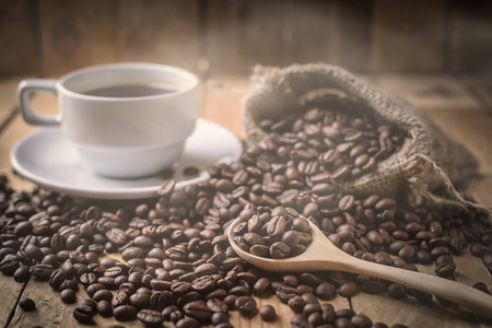 Attar: warm coffee cup and beans on brown background Stock Photo