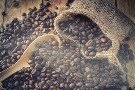 golden bean: Beans coffee in sack bag smell on wood background