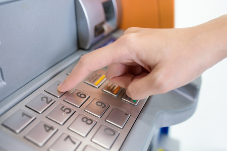 atm card: Close-up of hand entering PINpass code on ATMbank machine keypad Stock Photo