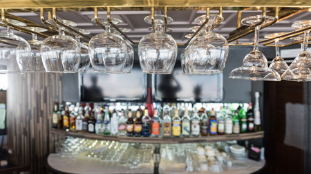 eatery: Empty glasses for wine above a bar rack in vintage tone. Stock Photo