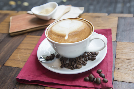edibles: Hot coffee on white cup on wood table fragrant coffee beans