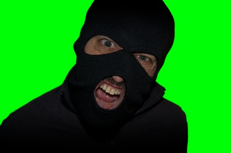 housebreaking: man close up thief in a mask and a blue shirt on a yellow background looks slyly to the camera. Mimicry. Photo shoot. Evil criminal wearing balaclava