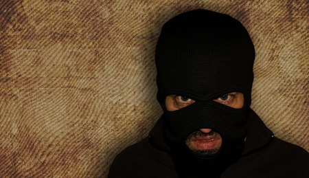man close up thief in a mask and a blue shirt on a yellow background looks slyly to the camera. Mimicry. Photo shoot. Evil criminal wearing balaclava