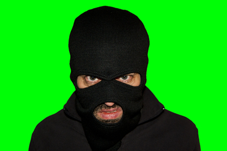 mimicry: man close up thief in a mask and a blue shirt on a yellow background looks slyly to the camera. Mimicry. Photo shoot. Evil criminal wearing balaclava