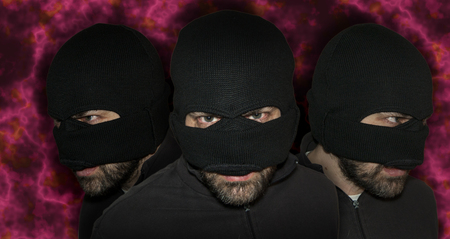 housebreaking: Three men close up thief in a mask and a blue shirt on a red background looks slyly to the fire. Mimicry. Photo shoot. Evil criminal wearing balaclava