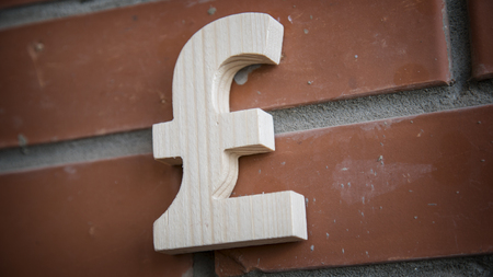 libra esterlina: Símbolo de la libra esterlina en una pared de ladrillo