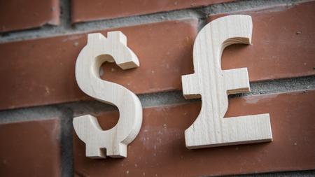libra esterlina: Valoraci�n de cambio. Moneda d�lar y la libra esterlina madera en una pared de ladrillo