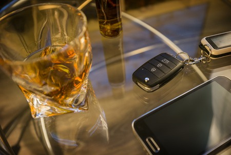 Glass of alcoholic drink and car key, on the table, on light background