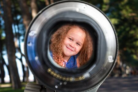 view through: Curly little blond girl portrait view through the lens