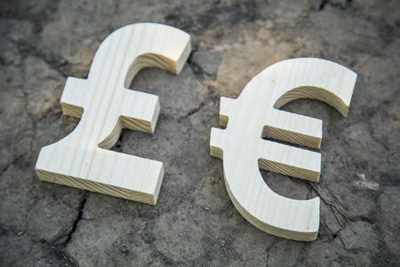 foreign land: Exchange currency euro and pound on a dry land. Wooden sign. Stock Photo