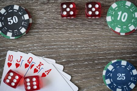 gambling counter: Gambling chips frame on wooden card table background Stock Photo