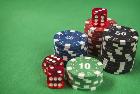 gambling counter: Gambling chips, red dice on green card table background