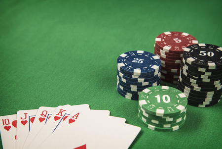 Gambling chips and flush royal on green card table background