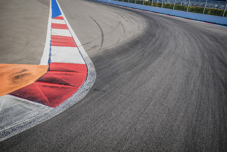 f1: Texture of motor race asphalt and red white curb. Close up on F1 Grand Prix street circuit