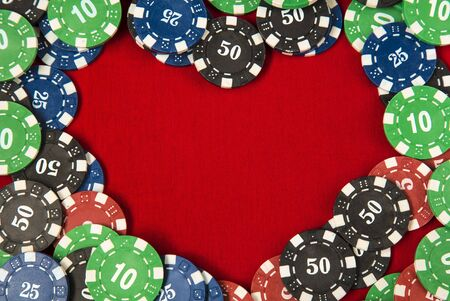 Gambling chips frame around the red card table background in the shape of a heart Stock Photo