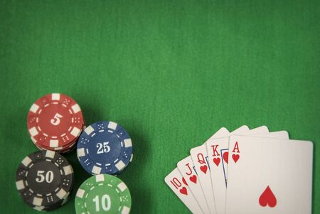 gambler: Gambling chips frame and flush royal on green card table background Stock Photo