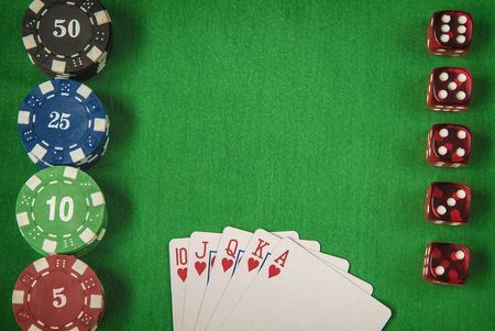 gambling counter: Gambling chips, red dice and flush royal on green card table background